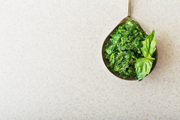 Homemade pesto sauce in spoon with basil on white table in kitchen. top view with copy space.