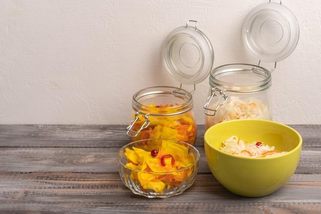 木製の背景に開いたふたとサラダ ボウルとガラスの瓶に自家製キャベツのピクルス