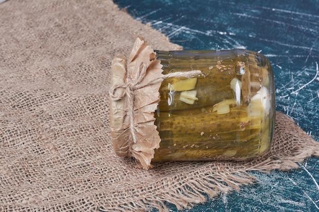 Cetrioli sottaceto fatti in casa in vaso di vetro sul blu con tovaglia di lana.