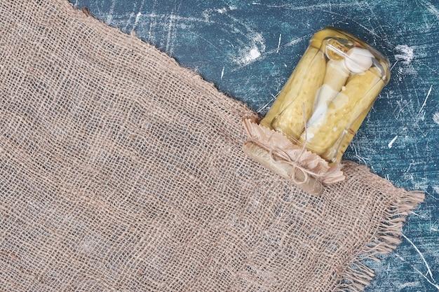 ウールのテーブルクロスと青のガラス瓶に自家製ピクルスきゅうり。