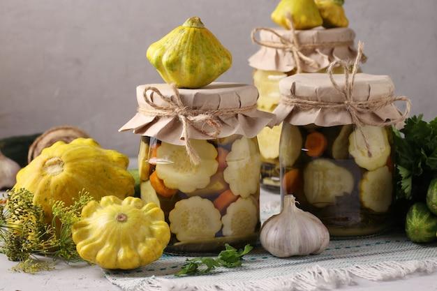 自家製の漬物パティパン、ニンジンとニンニクをガラスの瓶に入れたキュウリ、明るい灰色の表面に新鮮な食材
