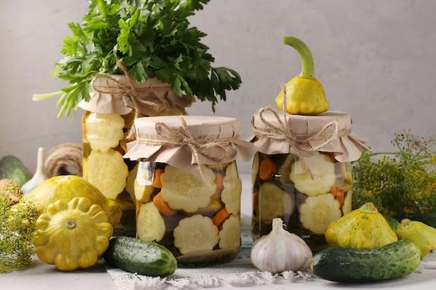 Домашние маринованные патиссоны, огурцы с морковью и чесноком в стеклянных банках и свежие ингредиенты