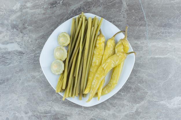 灰色の背景の上に自家製の漬物野菜の息子の白いセラミックプレート。