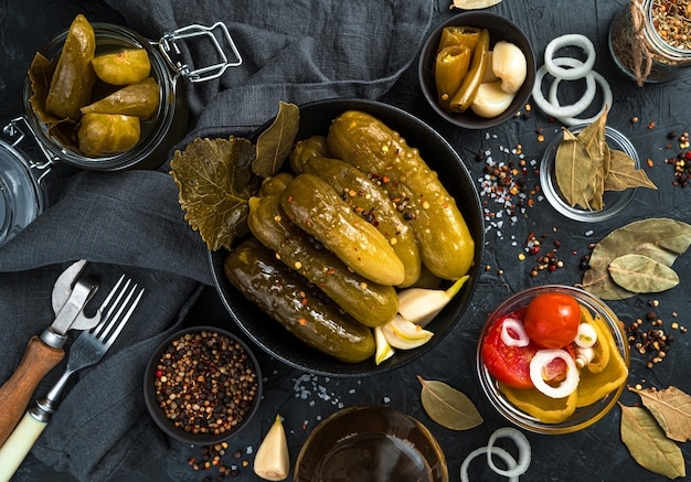 Homemade pickles, spices and garlic on a black background. top view, horizontal.
