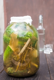 ガラスの瓶にスパイスとハーブを入れた自家製の漬物。背景にはウォッカのボトルとグラス2杯があります。