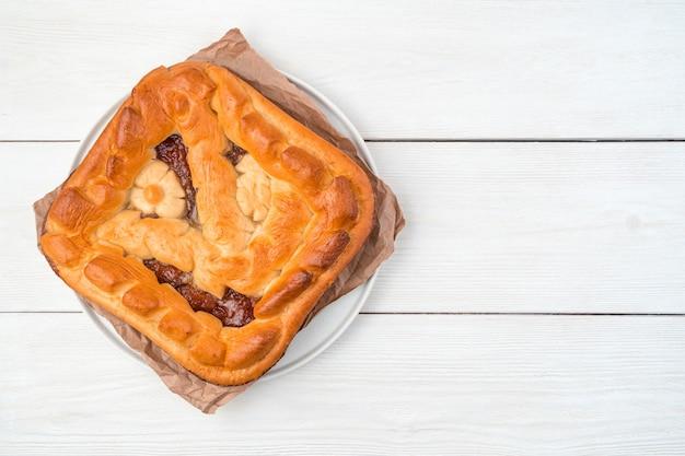Домашний пирог с яблочной начинкой на плоской тарелке с крафт-бумагой на светлом фоне.