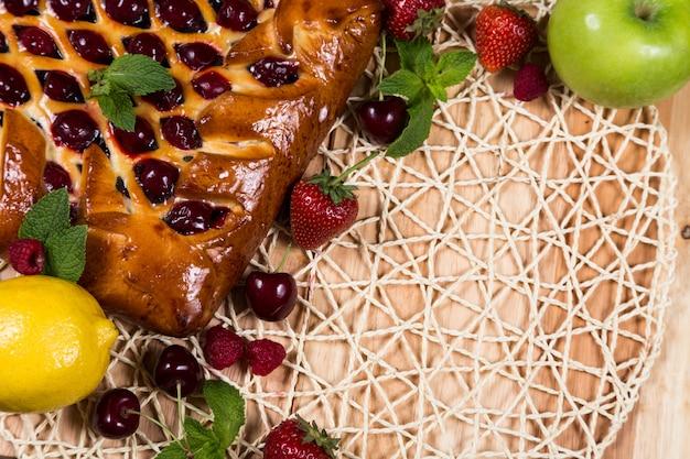 Домашний пирог с ягодами на фоне плетеной корзины
