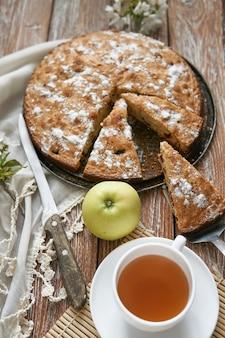 チェリーと自家製のパイと暗い素朴な木の板の背景にお茶の白いカップ。素朴なスタイルの料理