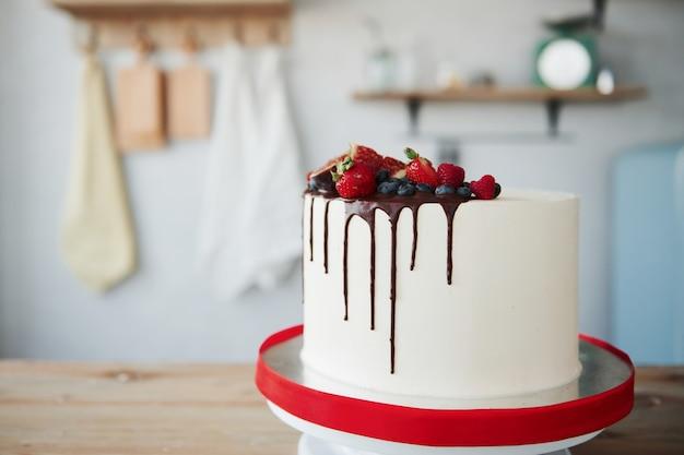 Домашний пирог с вишней и шоколадом на нем в помещении на кухне.