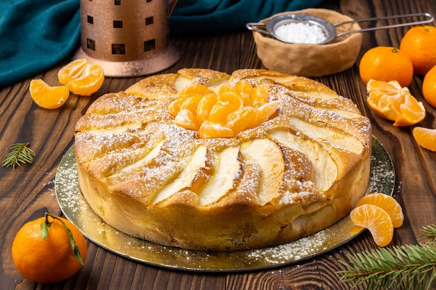 Homemade pie with mandarins and tangerines on rustic wooden table