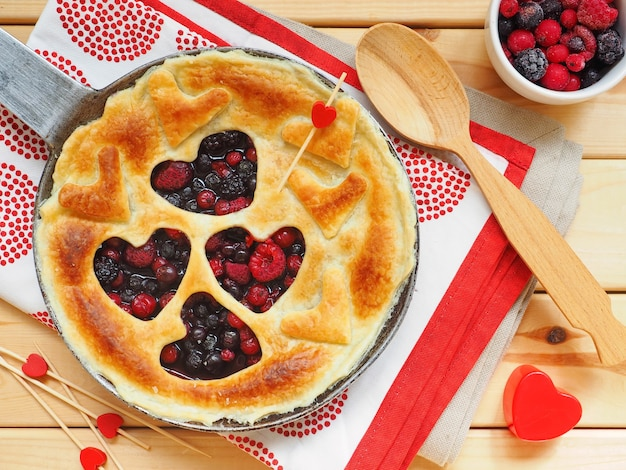 Homemade pie with raspberries, red currants and blueberries in shape of heart on wooden surface