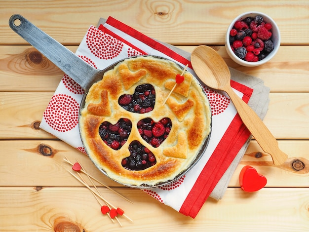 Homemade pie with raspberry, red currant and blueberry in shape of hearts.