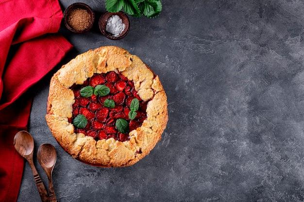 회색 배경 위에 딸기를 얹은 홈메이드 파이, 베리 사진이 있는 여름 페이스트리