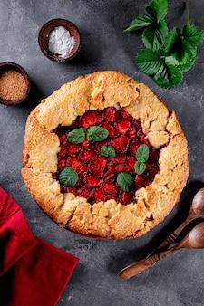 회색 배경 위에 딸기를 얹은 홈메이드 파이, 수직 딸기가 있는 여름 패스트리