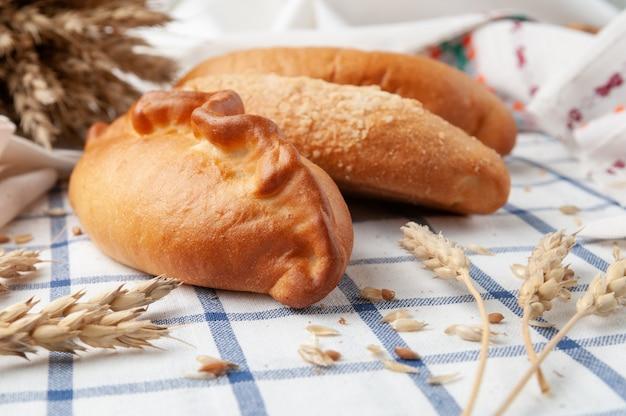 自家製パイ。青い cage a cageの中の白いテーブルクロスの上。背景には小麦の穂と穀物。