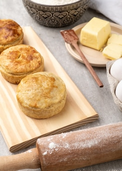 Homemade pies over wooden board with ingredients.