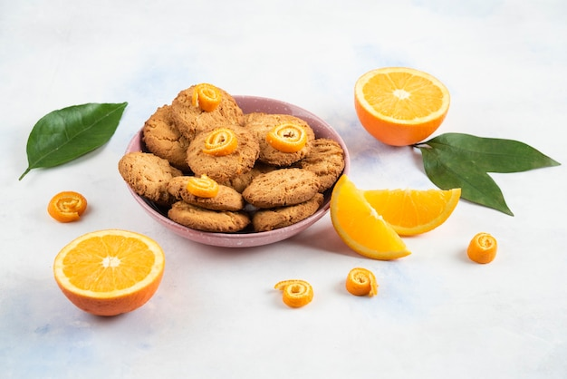 Homemade pile of cookies in pink bowl and orange sliced or half cut over white surface.