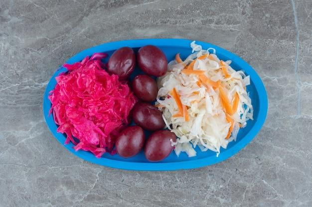 Mucchio casalingo di crauti sul piatto di legno blu
