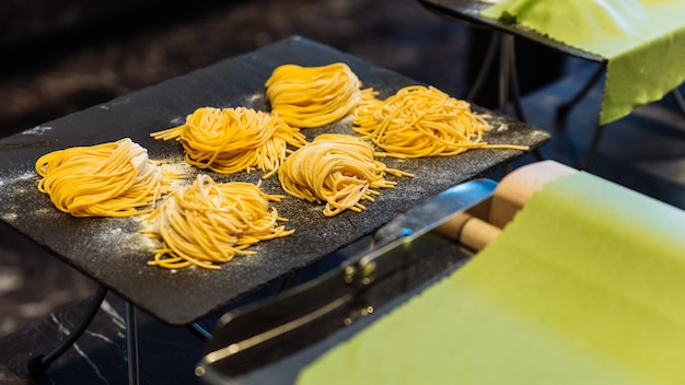 Homemade piles of fresh egg spaghetti pasta that powdering flour to keep them from sticking