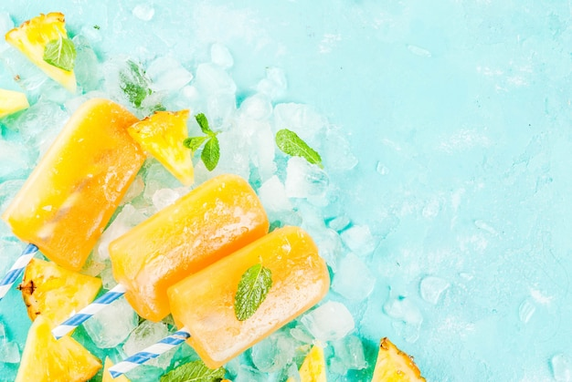 Homemade pineapple popsicles on ice with fresh pineapple slices and mint on light blue background