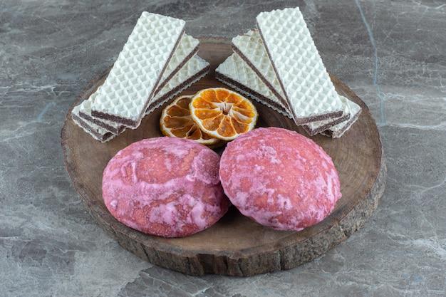 Biscotti rosa fatti in casa con wafer e fette d'arancia secche su tavola di legno.