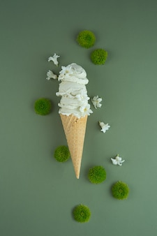 Homemade pistachio ice cream in a waffle cone and green and white flowers on green background