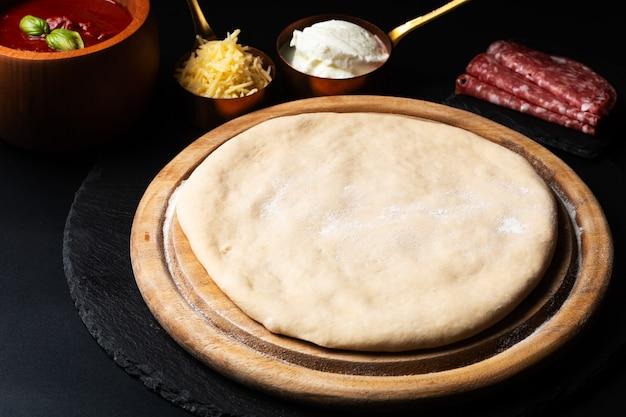 Домашнее тесто для пиццы на деревянной доске на черном фоне