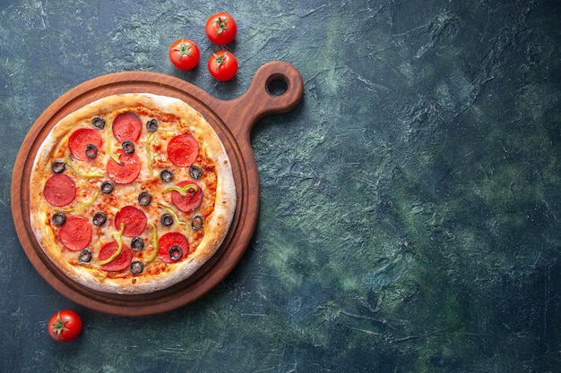 木製のまな板に自家製ピザと孤立した暗い表面にトマト