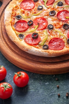 Домашняя пицца на деревянной разделочной доске и помидоры на изолированной темной поверхности