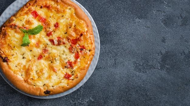Домашняя пицца лепешка с помидорами и сыром на сером фоне бетона.