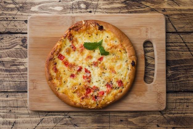 Домашняя пицца лепешка с помидорами и сыром на деревянных фоне. копировать пространство