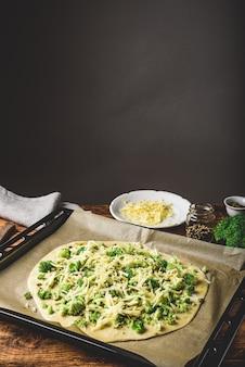 Домашняя пицца с брокколи, соусом песто, специями и сыром на противне, готовая к запеканию в духовке