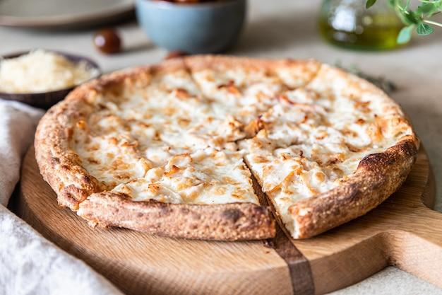 Домашняя пицца с курицей и сыром на светлой бетонной поверхности с белым соусом