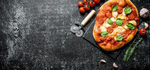 Homemade pizza with garlic cloves, tomatoes and rosemary. on dark rustic background