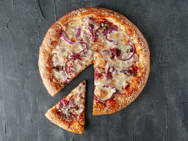 Homemade pizza with hunting sausages, pickled red onions, mushrooms, mozzarella cheese and tomato sauce. a piece is cut off from pizza. view from above. on a gray concrete background. isolated.
