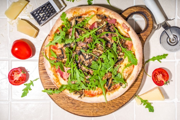 Homemade pizza with mushrooms, bacon, arugula and cheese, on tile summer sunny background. girl's hands in pic cuts and takes a slice of pizza top view