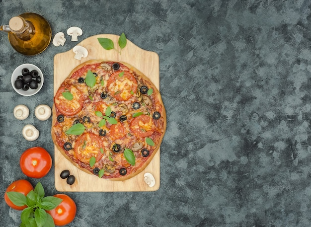 Homemade pizza with mushrooms, olives and ingredients on black background with copy space