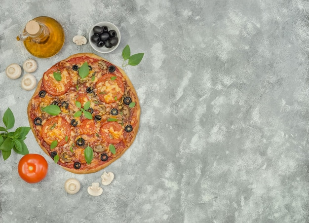 Homemade pizza with mushrooms, olives and ingredients on gray background with copy space
