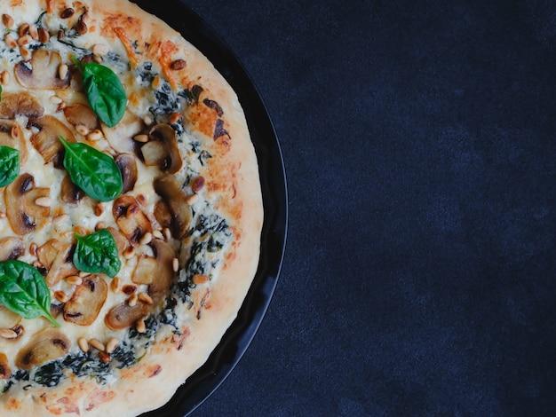 きのこ、ほうれん草、にんにく、クリームチーズ、松の実を使った自家製ピザ