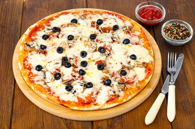 Homemade pizza with pepperoni, mushrooms, mozzarella and olives.