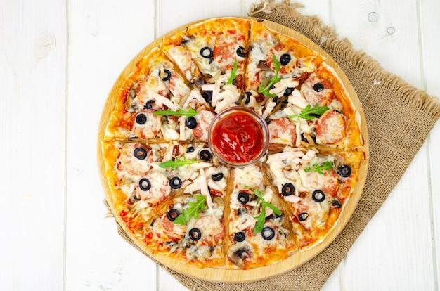木製のテーブルにサラミ、ハム、モッツァレラチーズを添えた自家製ピザ。スタジオ写真