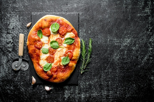 Homemade pizza with sausages, cheese and spinach on dark rustic table