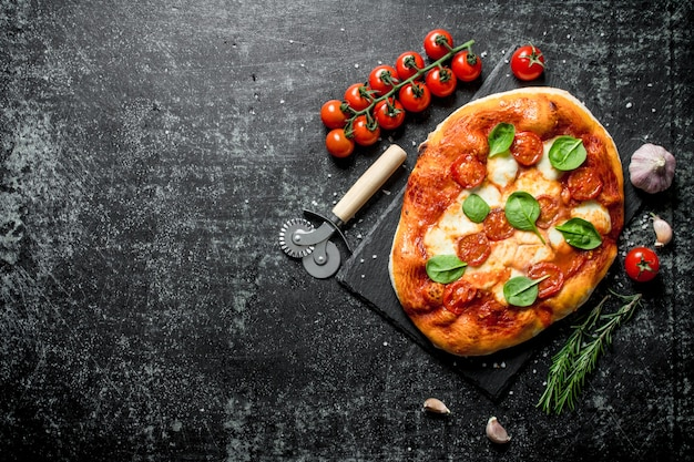 Homemade pizza with tomatoes on a branch and rosemary on dark rustic table.