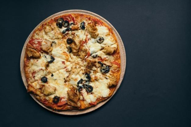 토마토, 모짜렐라, 바질을 곁들인 홈메이드 피자. 어두운 석재 테이블에 복사 공간이 있는 상위 뷰