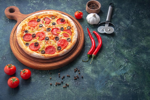 Homemade pizza on wooden cutting board and pepper garlic tomatoes on dark surface