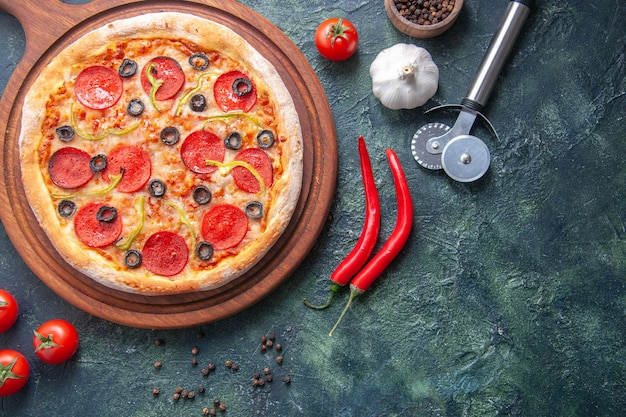 Homemade pizza on wooden cutting board and pepper garlic tomatoes on isolated dark surface in close up shot