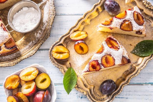 木製のテーブルの上のビンテージプレートの自家製プラムケーキ。プラムは砂糖粉でパイします。