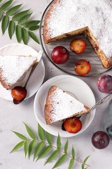 明るい背景のクローズアップのプレートにカットピースと自家製プラムパイ。ケーキに粉砂糖をまぶします。上から見る