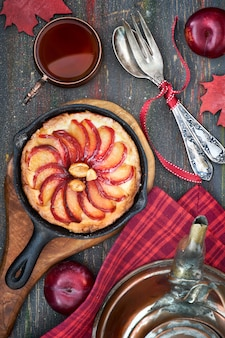 Homemade plum tart baked in iron cast skillet served with peanuts on wooden board