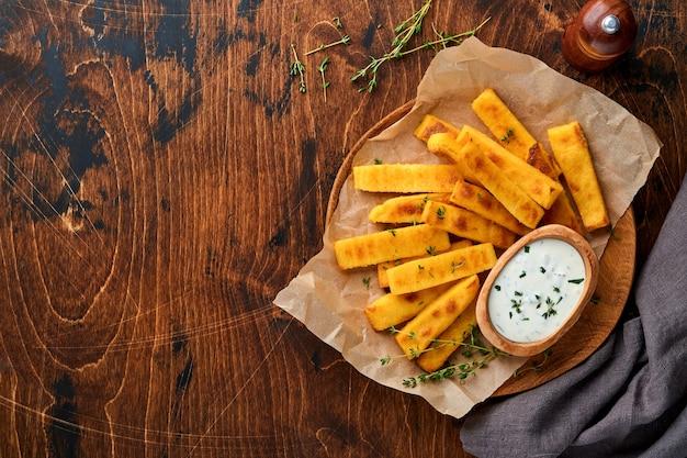 自家製ポレンタチップスは、海塩、パルメザンチーズ、タイム、ローズマリーとヨーグルトソースで揚げます。典型的なイタリアの揚げポレンタ。とうもろこしの炒め物。木製の背景。上面図